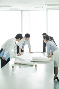 テーブルに図面を広げて打ち合わせをするビジネスマンとビジネスウーマンの写真素材 [FYI01623220]