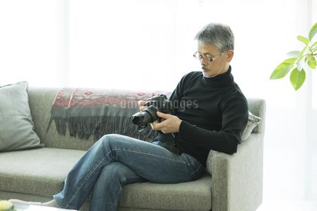 一眼レフカメラを触るシニア男性の写真素材 [FYI01623223]