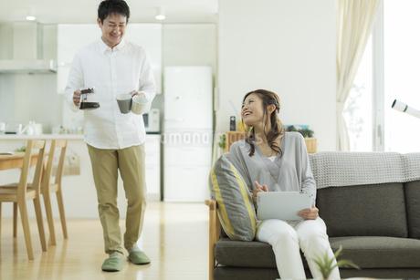 ソファーに座る妻とコーヒーを運ぶ夫の写真素材 [FYI01623225]