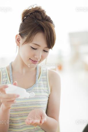 化粧品を手に出す若い女性の写真素材 [FYI01623232]