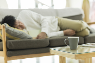 テーブルに置かれたカップとソファーで昼寝をする男性の写真素材 [FYI01623251]
