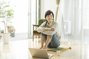 床に座る笑顔の女性の写真素材 [FYI01623254]