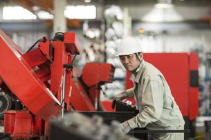 機械を操作する作業服の男性の写真素材 [FYI01623255]