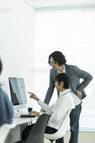 パソコンのモニターを見ながら打ち合わせをするビジネスマンの写真素材 [FYI01623262]