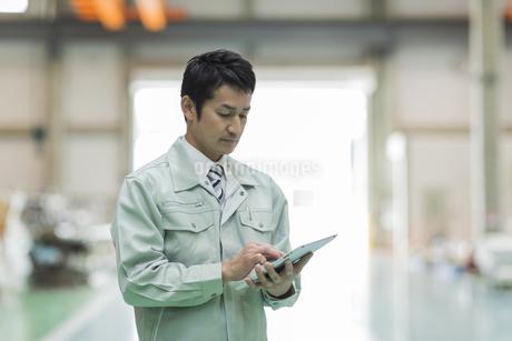 タブレットPCを操作する作業員男性の写真素材 [FYI01623266]