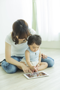 母親とタブレットPCで遊ぶ赤ちゃんの写真素材 [FYI01623276]