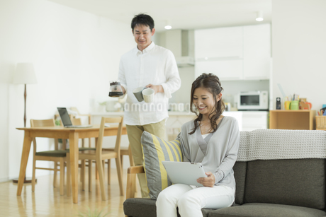 タブレットPCを見る妻とコーヒーを運ぶ夫の写真素材 [FYI01623279]