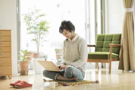 床に座ってパソコンをする女性の写真素材 [FYI01623284]