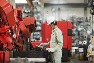 機械を操作する作業服の男性の写真素材 [FYI01623296]