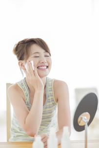 コットンを頬にあてて微笑む若い女性の写真素材 [FYI01623298]
