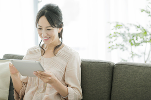 タブレットPCを操作する女性の写真素材 [FYI01623327]