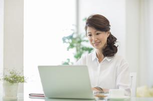 室内でパソコンをする中高年女性の写真素材 [FYI01623330]