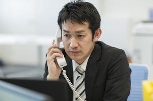 デスクで電話をするビジネスマンの写真素材 [FYI01623335]