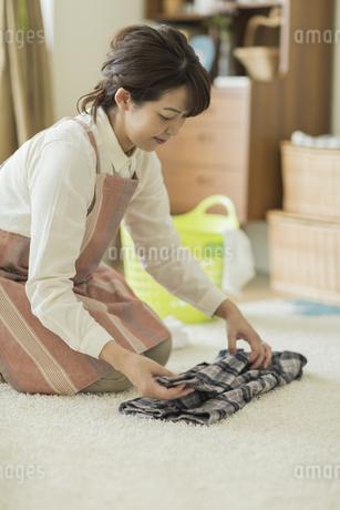 洗濯物を畳む女性の写真素材 [FYI01623338]