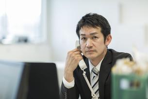 デスクで電話をするビジネスマンの写真素材 [FYI01623360]