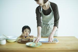 食器を片付ける母親と男の子の写真素材 [FYI01623363]