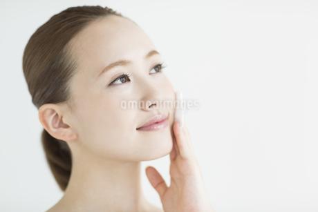 顔にコットンあてるスキンケアイメージの写真素材 [FYI01623364]
