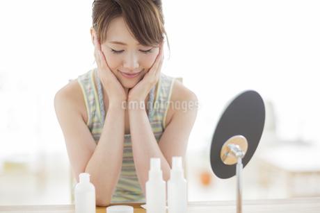 頬に両手をあてる若い女性の写真素材 [FYI01623368]