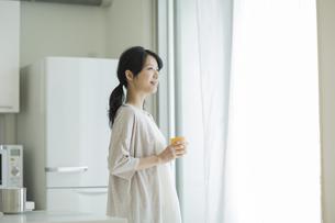 カップを持って外を眺める女性の写真素材 [FYI01623372]