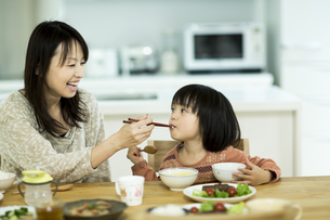 母親に食べさせてもらう女の子の写真素材 [FYI01623377]