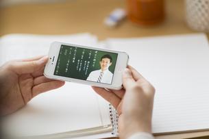 スマートフォンを見て勉強をする女子学生の手元の写真素材 [FYI01623401]