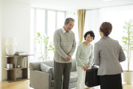 リビングでビジネスウーマンと会話をするシニア夫婦の写真素材 [FYI01623403]