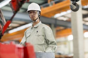 機械を操作する作業服の男性の写真素材 [FYI01623433]