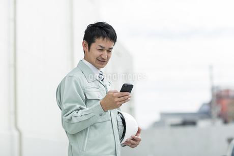 スマートフォンを操作する作業着の男性の写真素材 [FYI01623451]