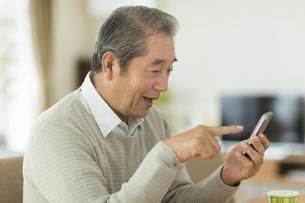 スマートフォンを操作するシニア男性の写真素材 [FYI01623452]