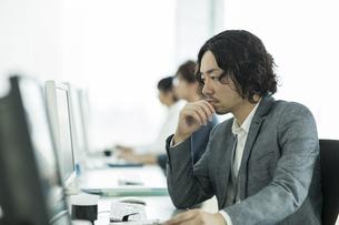 パソコンのモニターを見つめるビジネスマンの写真素材 [FYI01623455]