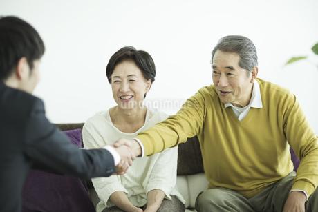 握手をするシニア夫婦とビジネスマンの写真素材 [FYI01623460]