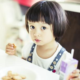 テーブルに座りお菓子を食べる女の子の写真素材 [FYI01623486]