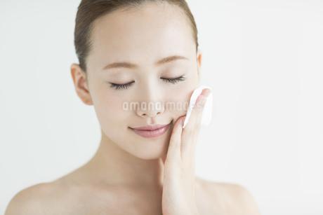 顔にコットンあてるスキンケアイメージの写真素材 [FYI01623491]