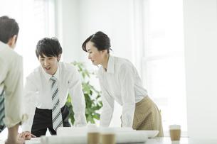 テーブルに図面を広げて打ち合わせをするビジネスマンとビジネスウーマンの写真素材 [FYI01623496]