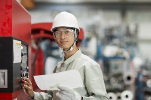 機械を操作する作業服の男性の写真素材 [FYI01623501]