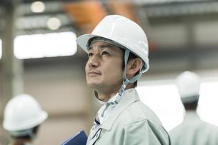 上を見上げる作業員男性の写真素材 [FYI01623504]