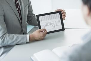 タブレットPCを使用して打ち合わせをするビジネスマンの写真素材 [FYI01623505]