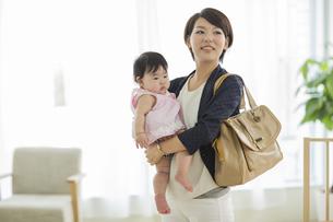 赤ちゃんを抱っこしながら出勤をする母親の写真素材 [FYI01623520]