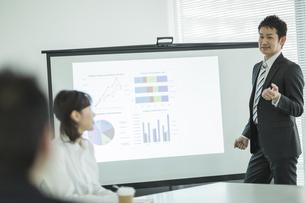 プロジェクターを使用した会議で説明をするビジネスマンの写真素材 [FYI01623543]