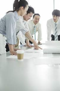 テーブルに図面を広げて打ち合わせをするビジネスマンとビジネスウーマンの写真素材 [FYI01623551]