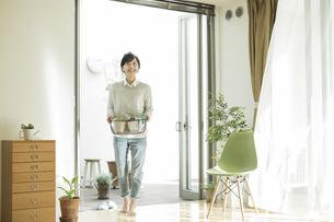 鉢植えを持って部屋に入る女性の写真素材 [FYI01623553]
