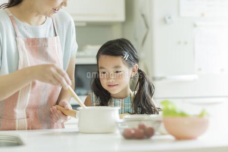 キッチンで料理をする母親に寄り添う女の子の写真素材 [FYI01623578]