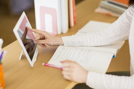 タブレットPCを使用して勉強をする女子学生の手元の写真素材 [FYI01623600]