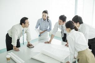 テーブルに図面を広げて打ち合わせをするビジネスマンとビジネスウーマンの写真素材 [FYI01623618]