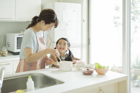キッチンで料理をする母親に寄り添う女の子の写真素材 [FYI01623630]