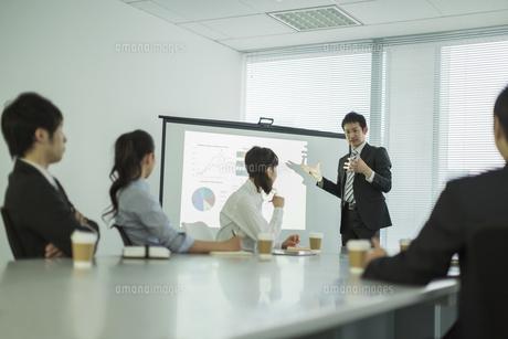 プロジェクターを使用した会議で説明をするビジネスマンの写真素材 [FYI01623638]