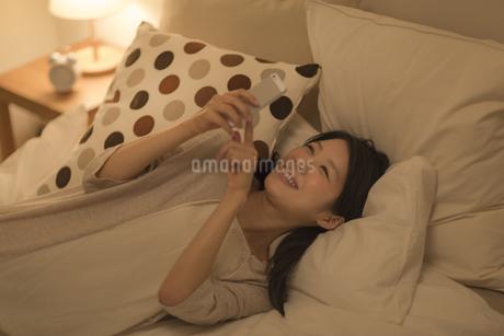 ベットに寝転んでスマートフォンを操作する女性の写真素材 [FYI01623640]