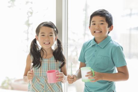 歯ブラシとコップを持って笑顔の兄と妹の写真素材 [FYI01623646]