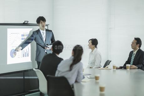 プロジェクターを使用した会議で説明をするビジネスマンの写真素材 [FYI01623649]