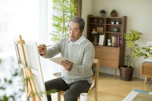 キャンバスに絵を描くシニア男性の写真素材 [FYI01623667]